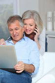 Senior couple at home surfing on internet — Stock Photo