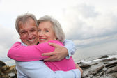 Happy senior couple embracing each other by the sea — Stock Photo