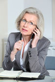 Portrait of senior businesswoman talking on the phone in office — Stock Photo