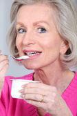 Portret senior kobiety jedzenie jogurt — Zdjęcie stockowe
