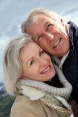 Portrait of happy senior couple at the mountain — Stock Photo
