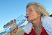 Active senior woman drinking water from bottle at the beach — Foto Stock