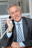 Portrait of senior businessman talking on the phone — Stok fotoğraf