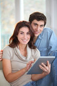 Young couple using electronic tablet at home — Stock Photo