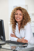 Businesswoman sitting at her desk in office — Stock Photo