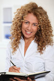 Businesswoman writing on agenda — Stockfoto