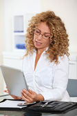 Businesswoman in office using electronic tab — Stock Photo