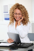 Businesswoman with electronic tab and mobile phone — Stock Photo