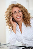 Portrait of woman with eyewear talking on the phone — Stock Photo