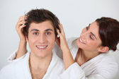 Young woman putting her hands in her boyfriend's hair — Stock Photo