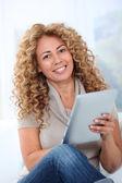Woman in sofa using electronic pad — Stock Photo