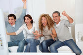 Group of friends sitting in sofa watching tv — Stock fotografie