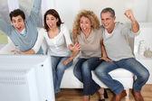 Skupina přátel, sedí v pohovce u televize — Stock fotografie