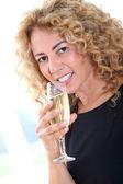 Beautiful woman holding glass of champagne — Stock Photo