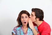 Young man whispering in his girlfriend's ear — Stock Photo