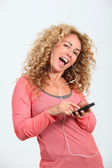 Portrait of blond woman listening to music player — Stock Photo