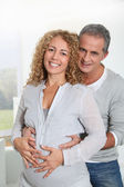 Parents with hands on pregnant woman's belly — Stock Photo