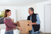 Young woman with removal man holding boxes — Stock Photo