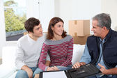Young couple signing contract for home moving — Stock Photo