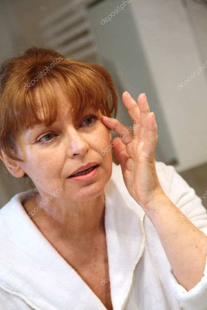 Portrait of senior woman applying moisturizing cream — Stock Photo #5695295