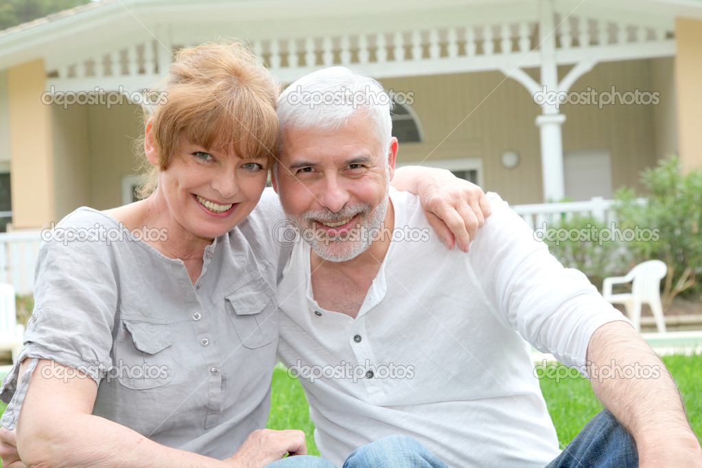 Portrait of senior couple standing in front of their home — Stock Photo #5695369