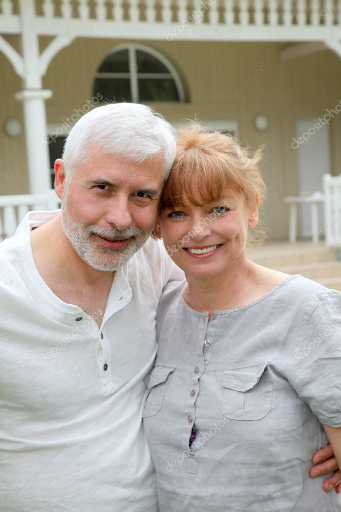 Portrait of senior couple standing in front of their home  Stock Photo #5695373