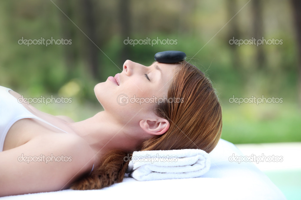 Woman laying on massage bed with hot stone on forehead — Stock Photo #5695851