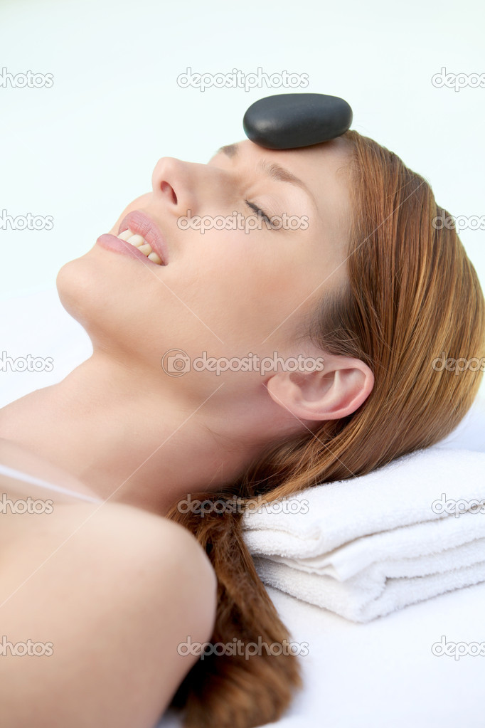 Woman laying on massage bed with hot stone on forehead  Stock Photo #5695852