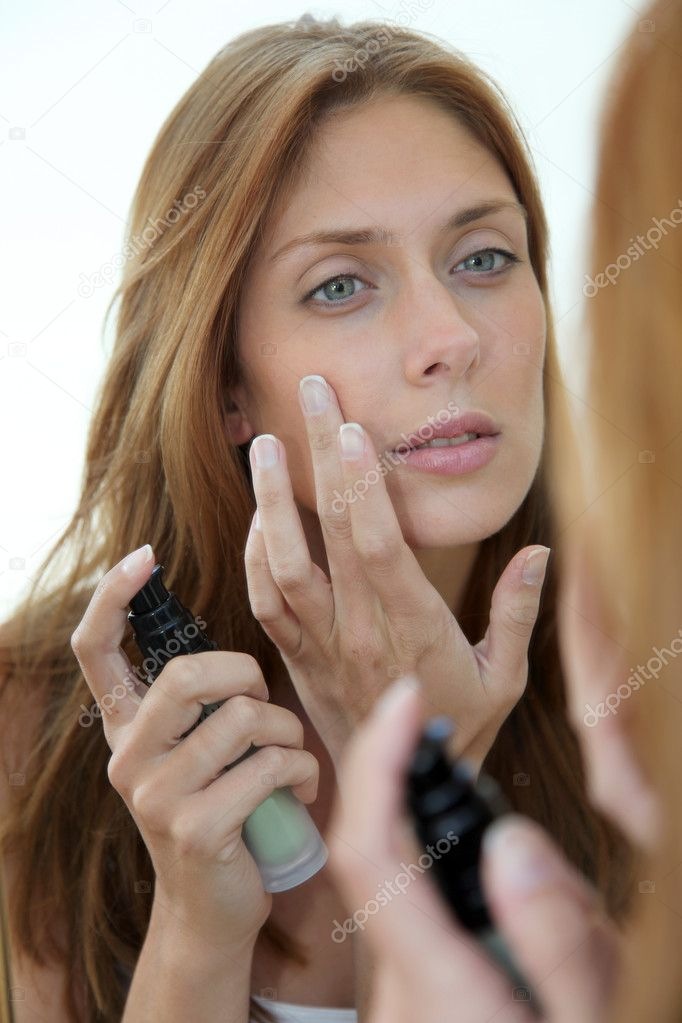 Beautiful woman putting foundation on her face — Foto Stock #5696139
