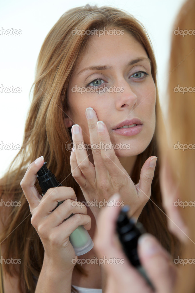 Beautiful woman putting foundation on her face — Lizenzfreies Foto #5696139