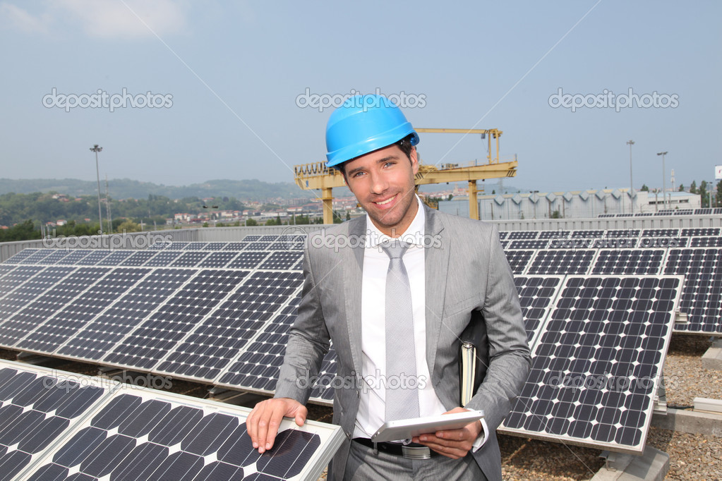 Businessman standing on solar panel installation — Stock Photo #5697281