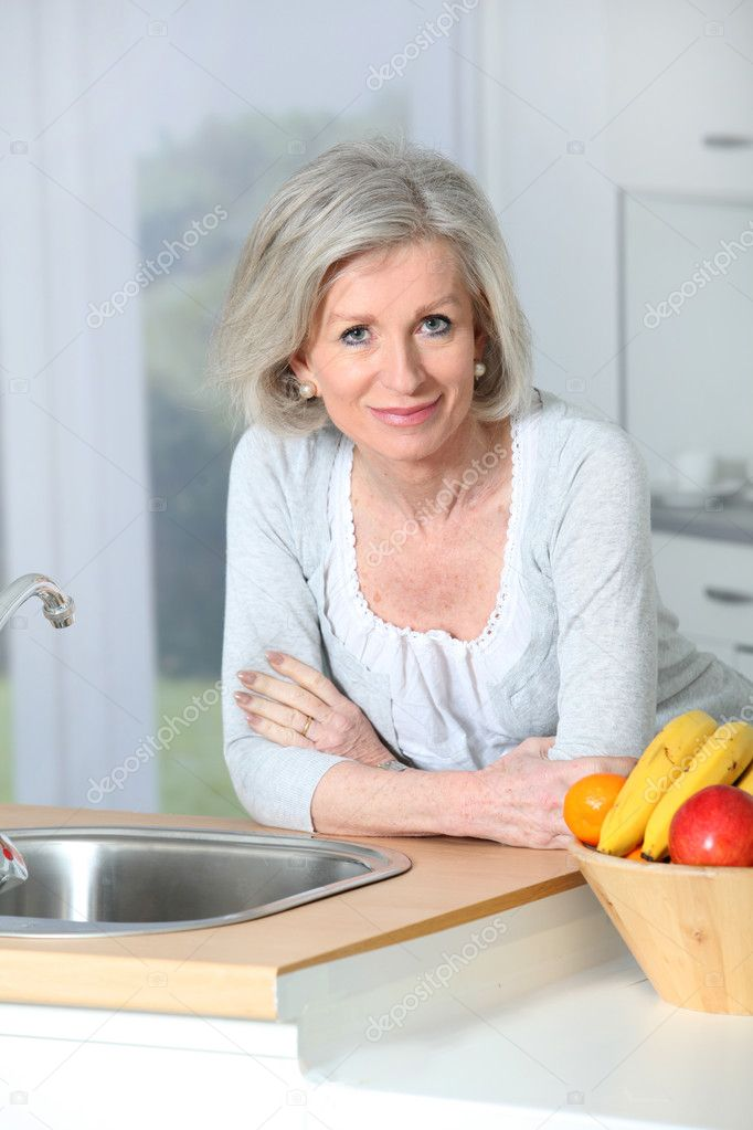 Senior woman standing in kitchen — Stock Photo #5697353