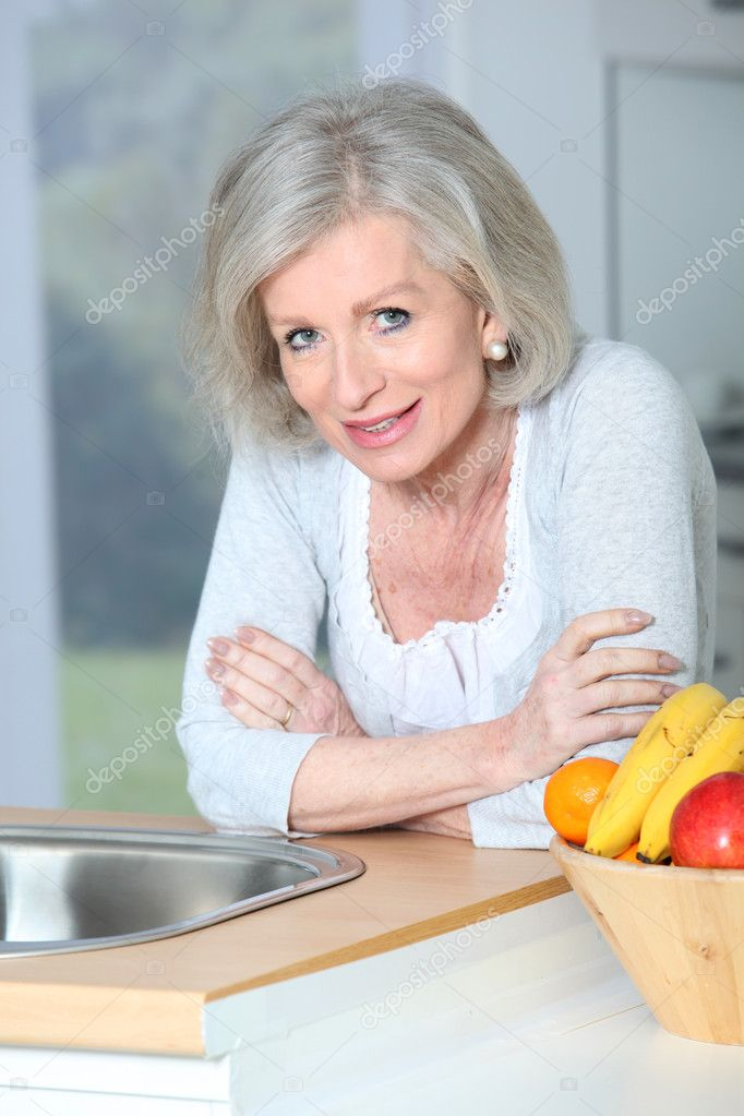 Senior woman standing in kitchen  Stock Photo #5697357