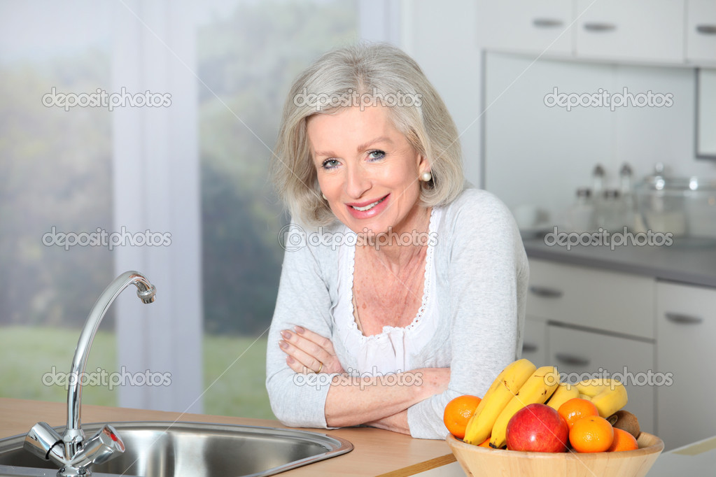 Senior woman standing in kitchen — Stock Photo #5697360