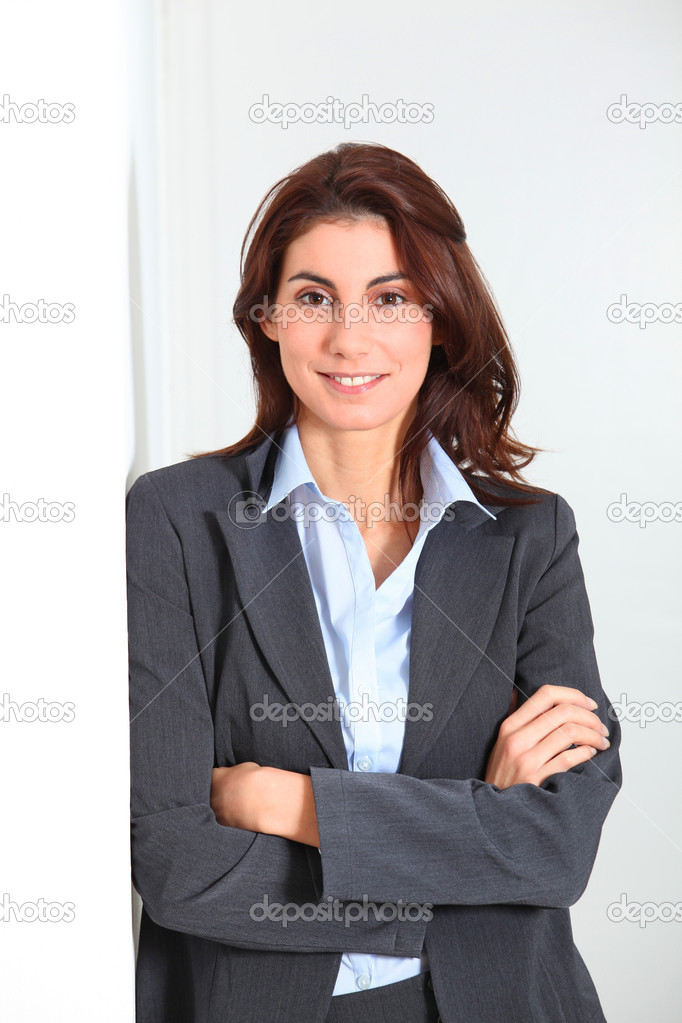 Businesswoman standing against white wall — Stock Photo #5698365