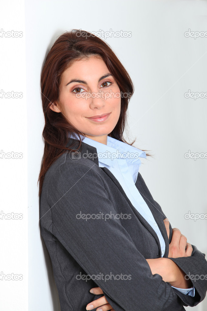 Businesswoman standing against white wall  Stock Photo #5698371