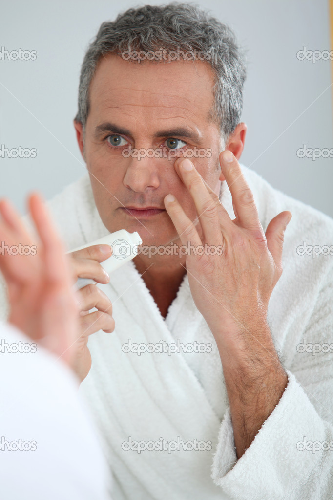Portrait of mature man applying moisturizer on his face — Stock Photo #5698678