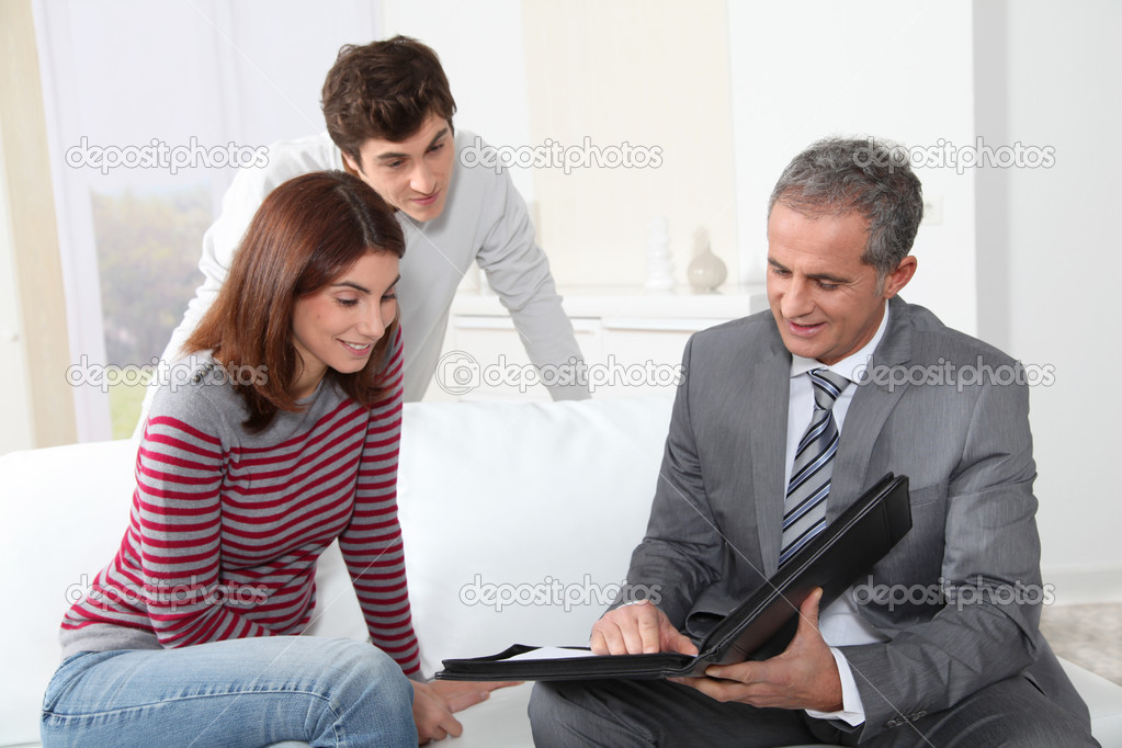 Young couple sigining renting contract with real estate agent — Stock Photo #5699779