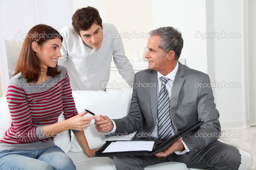 Young couple sigining renting contract with real estate agent — Stock Photo #5699780