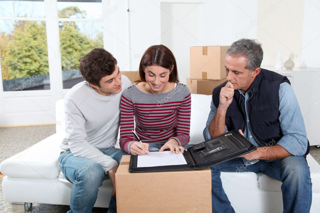 Young couple signing contract for home moving — Stock Photo #5699793