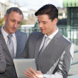 Business partners working on electronic tablet — Stock Photo