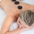 Woman laying on massage bed with hot stones on her back — Stock Photo #5700672