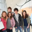 Stock Photo: Portrait of teenagers and teachers standing on school hall