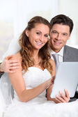 Bride and groom doing shopping on inernet — Stock Photo