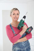 Beautiful blond woman holding electric drill — Stock Photo
