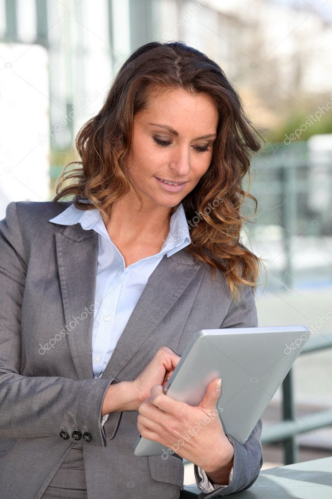 Smiling businesswoman using electronic tablet outside — Stock Photo #5700053