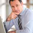 Portrait of businessman in front of laptop computer — Stock Photo #6697461