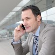 Salesman talking on the phone outside congress center — Stock Photo #6697756