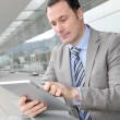Businessman using electronic tab outside congress center - Stock Photo