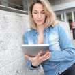 Beautiful woman using electronic tab in the street — Stock Photo